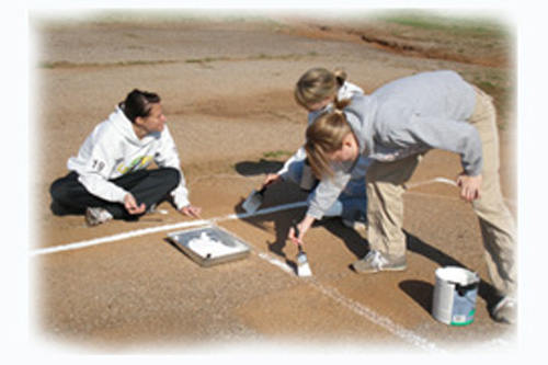 Women painting baseball field